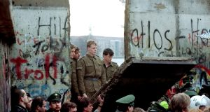 East German border guards look through a hole in the Berlin Wall after demonstrators pulled down the segment at the Brandenburg Gate in Berlin. Photograph: Lionel Cironneau/File/AP Photo