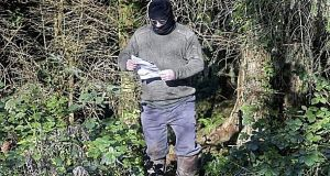 A photograph of a man appearing to read out the latest death threat against the directors of Quinn Industrial Holdings. Photograph: Courtesy of the Irish News