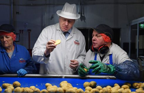 British prime minister Boris Johnson checks a potato as he helps quality control staff during a general election campaign visit to the Tayto Castle crisp factory in Co Armagh. Photograph: Daniel  Leal-Olivas/Getty