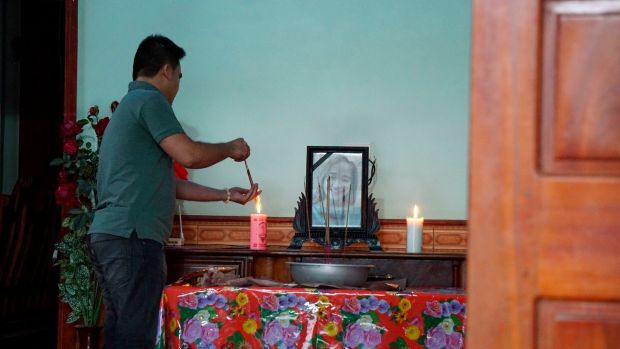 Bui Thi Nhung (19) was also confirmed to be among the dead. Here a family member lights incense sticks from a candle at an altar with Nhung's portrait inside her home home in Do Thanh village, Nghe An province, Vietnam. Photograph: AP Photo/Linh Do