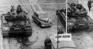 A car rides between US tanks, in October 1961, across the border at the Berlin Wall between East (Soviet sector). Photograph/AFP/Getty