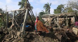 A woman cleans her house damaged by Cyclone Bulbul in Bakkhali. Photograph: Dibyangshu Sarkar/AFP