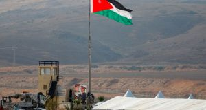 A picture taken from the Israeli side of the border shows Jordanian soldiers raising the national flag ahead of a ceremony at the Jordan Valley site of Naharayim, also known as Baqura in Jordan. Photograph:  Menahem Kahana/AFP via Getty