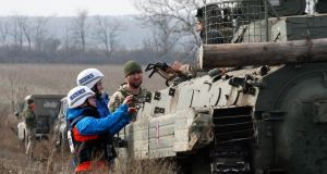 OSCE observers check a Ukrainian serviceman's weapons during the forces' disengagement near Bohdanivka village, Ukraine, at the weekend. Photograph: Vadim Kot/EPA