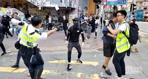 UNREST CONTINUES: A still image from a social media video shows a police officer aiming his gun at a protester in Hong Kong.  Photograph: Cupid Producer/Reuters