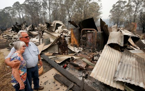 WILDFIRES AFTERMATH: Lyn and Peter Iverson with their burnt out office and shed on their property at Half Chain road, Koorainghat, Australia. Photograph: AAP Image/Darren Pateman/Reuters