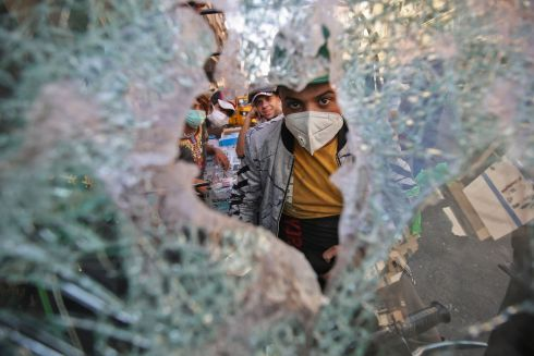 BROKEN SOCIETY: A protestor looks through a pane of shattered glass during anti-government demonstrations at Khallani square in Baghdad, Iraq. Photograph: Ahmad Al-Rubaye/AFP/Getty