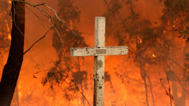 A bushfire burns behind a cross at Possum brush, near Taree, New South Wales. Photograph: EPA/DARREN PATEMAN