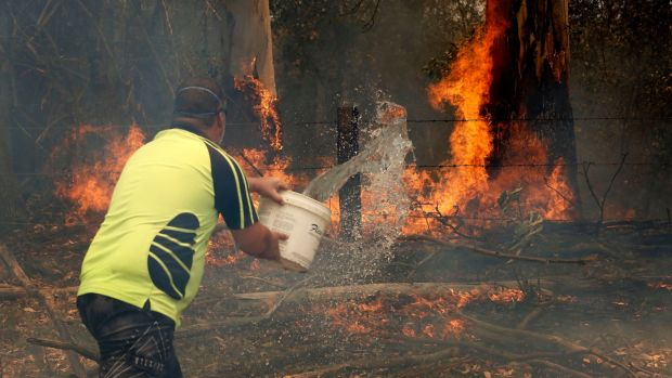 A resident tries to contain a fire at Koorainghat, near Taree, New South Wales. Photograph: Darren Pateman/EPA