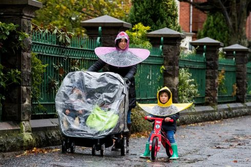BE PREPARED: Parichat Sae-Lao walks in the rain with her daughter Daisy and other children in Belfast after heavy overnight rain caused localised flooding in parts of Northern Ireland. Photograph: Liam McBurney/PA Wire