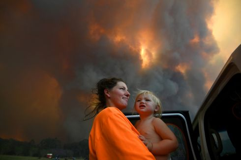 BUSHFIRE THREAT: Sharnie Moren and her 18-month-old daughter Charlotte watch as thick smoke rises from bushfires near Nana Glen, near Coffs Harbour, Australia. Photograph: Dan Peled/AAP/Reuters