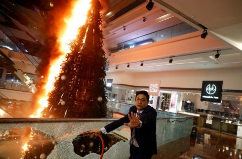 NO RESPITE: A man tries to extinguish a burning Christmas tree at Festival Walk mall in Kowloon Tong, Hong Kong, China, amid continuing political unrest there. Photograph: Thomas Peter/Reuters