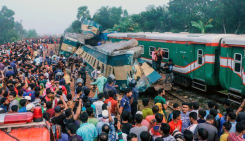 TRAIN COLLISION: Bystanders look on after a train collided with another in Brahmanbaria, some 130km from Dhaka, Bangladesh,. The two packed locomotives rammed into each other, killing at least 16 people and injuring nearly 60 others, police said. Photograph: AFP/Getty