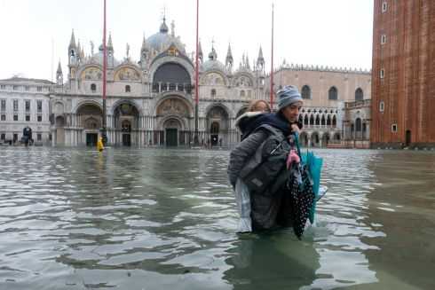 FLOOD-PRONE: A woman makes her way through floodwater while carrying a child in St Mark's Square, Venice, Italy.  Photograph: Manuel Silvestri/Reuters
