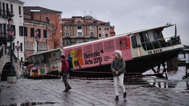 People walk past a stranded taxi boat on Riva degli Schiavoni in Venice on Wednesday after an exceptional overnight high tide of 187cm was recorded in the Italian lagoon city. Photograph: Marco Bertorello/AFP via Getty Images.