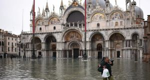 A man wearing waders  crosses St Mark's square and passes  St Mark's Basilica in Venice on Wednesday after an exceptional overnight high tide  of 187cm was recorded in the Italian lagoon city. Photograph:  Marco Bertorello/AFP via Getty Images.