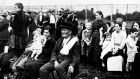 An Irish immigrant sits on a chair next to an Italian and her children at Ellis Island in the early 20th century. Photograph:  FPG/Getty Images