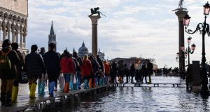 People walk on a footbridge across  St Mark's Square to keep dry. Photograph: Filippo Monteforte/AFP via Getty