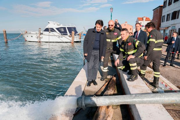 Italy's prime minister Giuseppe Conte (centre) looks on as water is pumped out while assessing damages after the city suffered its highest tide in 50 years. Photograph: Filippo Attili/Palazzo Chigi press office/AFP via Getty