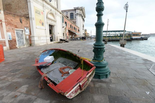 A boat is left stranded on the quayside following the high tide. Photograph: Andrea Merola/EPA