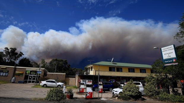 Smoke rising from a bushfire on Gospers Mountains looms over Colo Heights, New South Wales. According to media reports, at least four people have been killed and hundreds of homes destroyed in wildfires. Photograph: EPA