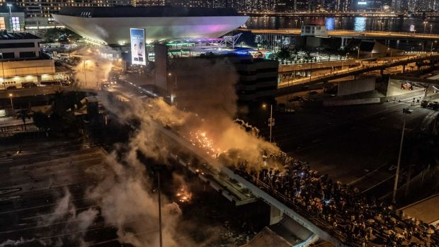 Protesters and police clash on a bridge at The Hong Kong Poytechnic University in Hong Kong. Photograph: Anthony Kwan/Getty Images.