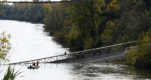 Rescuers sail near a suspension bridge which collapsed near Toulouse, southwest France. Photograph:  Eric Cabanis/AFP