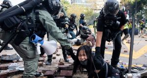 Police detain a woman during a protest in the Tsim Sha Tsui district of Hong Kong on Monday. Photograph:  Kyle Lam/Bloomberg