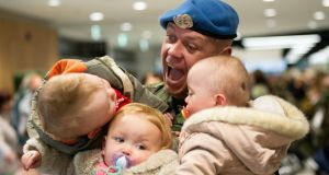 FALL IN...ON THE TRIPLE: Cpl Christopher McMahon, from Dundalk, with his triplets James, Nicole and Emily (17 months), at Dublin Airport after his return from duty in Lebanon. He is one of  of 232 Irish troops from the 114th Infantry Battalion serving with the United Nations Interim Force in Lebanon (UNIFIL) who returned. Photograph: Tom Honan