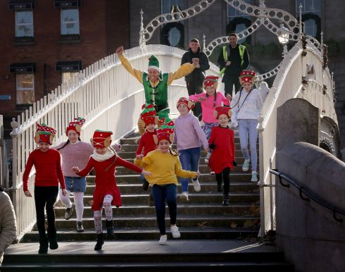 CHRISTMAS CRACKER: Buddy the Elf (Tam Ryan) on the Ha'Penny Bridge in Dublin with Kaya Godley, Chloe Brennan, Laoibhse O'Grady, Darci Gormley, Sarah Benzies, Katie Rice, Eryn Gormley, Ruby Glynn Clarke and Kiya O'Rourke, some of the children who will be performing with him, Kym Marsh and Shaun Williamson in  'Elf - A Christmas Spectacular, at 3Arena. Photograph: Mark Stedman