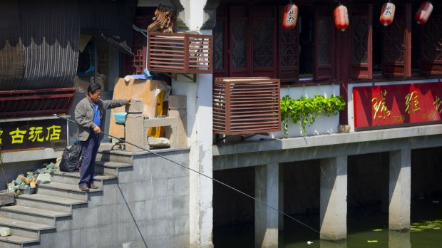 A man is standing on the stairs of a tea house and fishing out of the river. Photograph: iStock