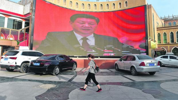 People walk past a screen showing images of China president Xi Jinping in Kashgar in China's western Xinjiang region, in June, 2019. Photograph: Greg Baker/AFP)