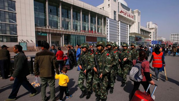 Armed policemen patrol near the exit of the railway station in Urumqi, Xinjiang in 2014. Photograph: Reuters/Petar Kujundzic)