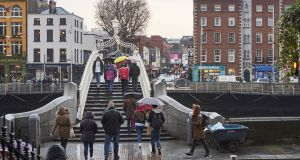 Pedestrians walking over Ha'penny Bridge, the main access point to the touristic area of Temple Bar. Photograph: iStock