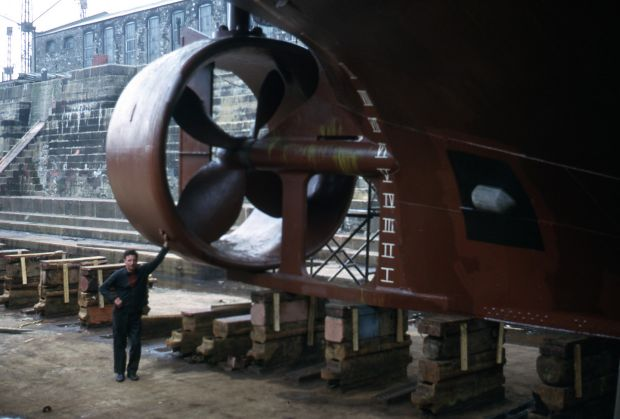 A dock worker stands alongside the propeller of a ship sitting in dry dock at the port. Photograph: Dublin Port Archive