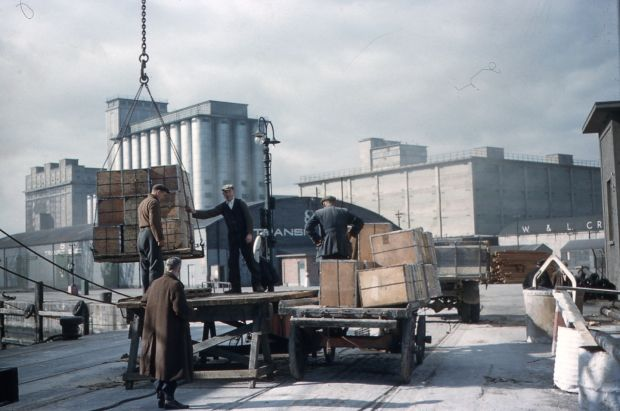 Cargo is loaded onto a trailer at the quayside as the Odlums Mill looms in the backgrounfd. Photograph: Dublin Port Archive