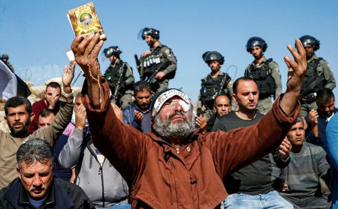 WEST BANK TENSIONS: Israeli soldiers watch as a man lifts up his hands in prayer while holding prayer beads and a copy of the Koran, during a demonstration in the village of Surif, north of Hebron in the occupied West Bank. The protest was attended by Palestinians and Israeli activists against Israeli confiscation of Palestinian lands and in solidarity with Palestinian cameraman Mu'ath Amarneh, who was injured in the eye by a rubber bullet while covering previous clashes. Photograph: Hazem Bader/AFP via Getty