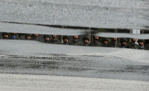 MILITARY MIRRORED: Royal Thai Marines gathered in formation are reflected on a pool of rain water in Chulabhorn Camp in Thailand's southern province of Narathiwat. Photograph: Madaree Tohlala/AFP via Getty