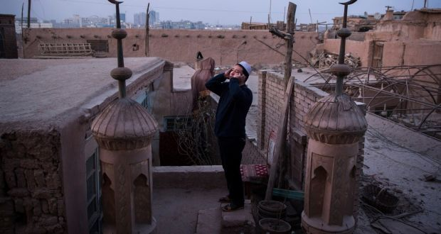 A muezzin sounds the call to prayer from the roof of a mosque in Kashgar in  Xinjiang. A million ethnic Uighurs have been corralled into internment camps and prisons. Photograph: Adam Dean/New York Times