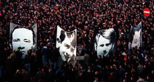 Pictures of the victims of Bloody Sunday being carried through the crowd of thousands after the 25th anniversary march for Bloody Sunday in Derry. Photograph: Brian Little/PA