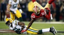 Wide receiver Emmanuel Sanders of the San Francisco 49ers is upended by strong safety Adrian Amos of the Green Bay Packers. Photo: Ezra Shaw/Getty Images