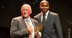 Irish coach Br Colm O'Connell receives the coaching achievement award from former world record holder Wilson Kipketer during the IAAF World Athletics Awards ceremony in Monaco.