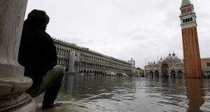 A man sits on steps of Museo Correr as water floods into St Mark's Square. Photograph: Alberto Lingria/Reuters
