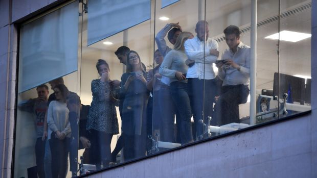 Office workers peer out of the windows of Leadenhall Market near London Bridge in central London. Photograph: Ben Stansall/AFP via Getty