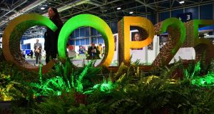 A visitors walks by the logo of the UN Climate Change Conference COP25 decorated with plants at the 'IFEMA - Feria de Madrid' exhibition centre, in Madrid, on Monday. Photograph: AFP via Getty Images