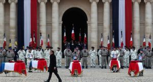 French president Emmanuel Macron  at   Les Invalides monument in Paris where he stood to  attention by the coffins of  13 French soldiers killed in Mali. Photograph: AP Photo/Thibault Camus, Pool