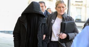 Lisa Smith (38) (left, covered) is escorted by a Garda member leaving the Criminal Courts of Justice, Dublin on Tuesday morning. Photograph: Collins Courts