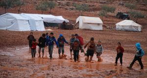 Children walk through a rainwater puddle in a flooded camp for displaced Syrians near the village of Killi in the north of the northwestern Idlib province. Photograph: Aaref Watad/AFP/Getty
