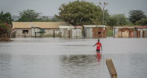 A man wades through water in Elegu, northern Uganda, on the border with South Sudan, where businesses and homes damaged by flooding. Photograph: Sally Hayden