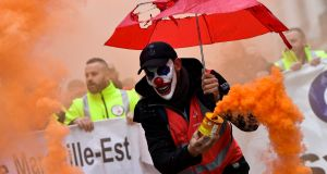 A man wearing a clown mask and waving a smoke bomb takes part in a demonstration against  pension overhauls, in Marseille,  France. Photograph: Clement Mahoudeau/AFP via Getty Images